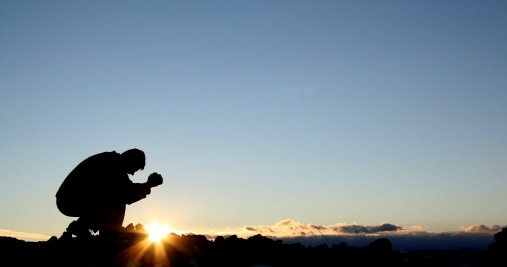 kneeling-in-prayer-at-sunrise